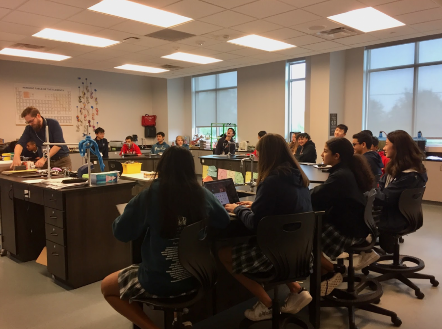Eighth-graders listening to biology teacher Wesley Adams as he presents parts of the high school science curriculum.