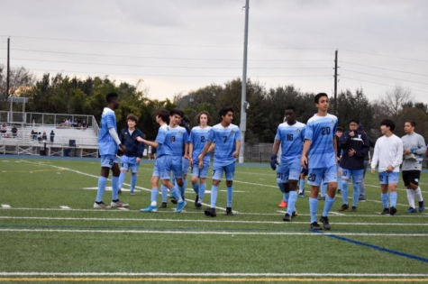 The Village School Junior Varsity soccer team gather on the field before a game against St. Thomas High School.