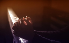 A picture of prayer hands laying on a bar
