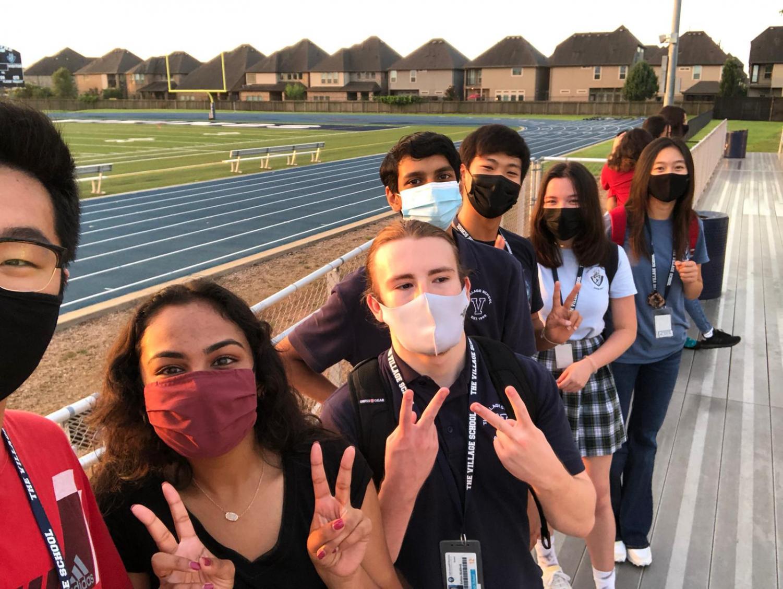 Tommy Wan(12), Esha Garg(12), Dalton Bickford(12), Arjun Bala-Mehta(12), Thomas Chin(12), Megan Gunter(12), and Zoe Nguyen(12) posing for a photo at the football field during the morning sunrise.